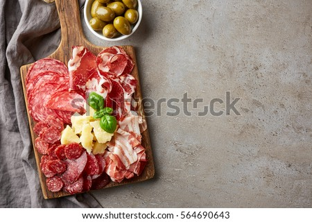 Shutterstock Wooden cutting board with prosciutto, salami and cheese on gray stone background. From top view