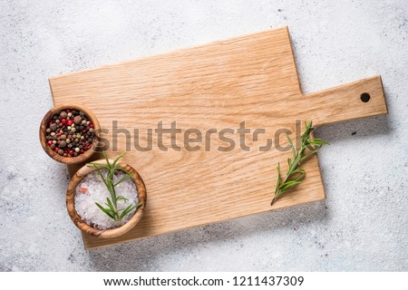 Wooden cutting board with sea salt and pepper on white stone table. Top view copy space. Stock foto ©
