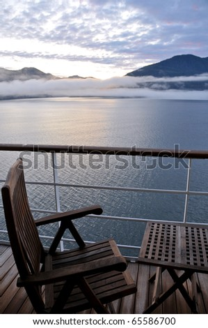 wooden deck chair and table on cruise ship in scenic alaskan passage at dawn