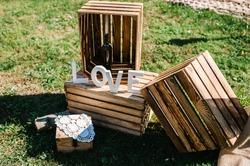 Wooden decor with the inscription love. Wedding decorations against the background of wooden box. Photo and lounge zone.