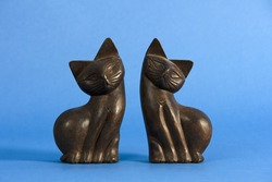 Wooden decorative figurines of couple of black cats against blue background