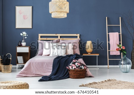 Wooden decorative ladder with pink blanket standing in cozy hotel bedroom