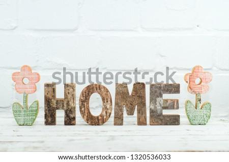 Wooden deko blumen with lettering Home in front of white brick wall Stok fotoğraf ©
