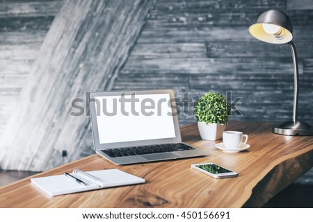 Wooden designer desktop with blank white laptop, stationery items, coffee cup, cell phone, plant and table lamp. Mock up
