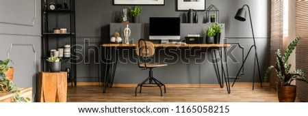 Wooden desk, fresh potted plants and mockup computer monitor standing in a dark grey living room interior with metal furniture #1165058215