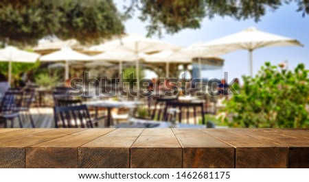 Photo of Wooden desk of free space for your decoration and blurred background of restaurant interior. Summer time.