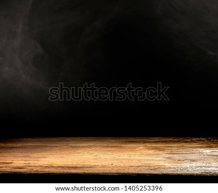 Wooden desk of free space for your decoration. Black background with space for your text. Smoke and mood photo.