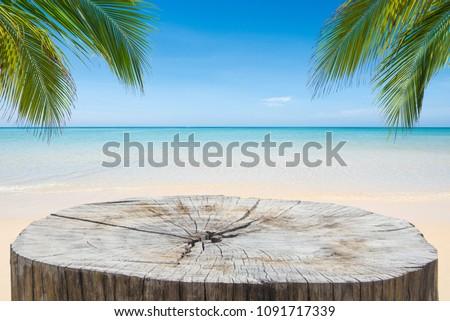 wooden desk or stump on sand...