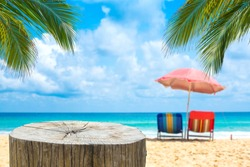 Wooden desk or stump on sand beach in summer,Beach chairs with umbrella  background.