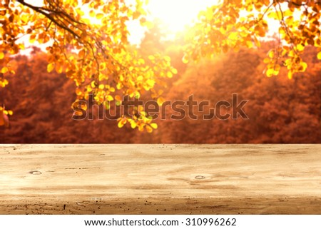wooden desk top and autumn leaves