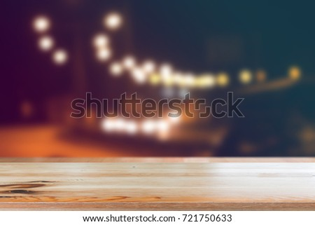 Shutterstock Wooden desk with Blurred light on road in city with bokeh abstract background