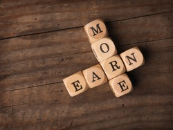 Wooden dices with the words Earn more on a rustic background, financial concept