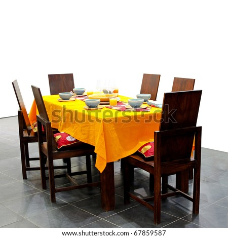 Wooden dining table for six with orange cloth