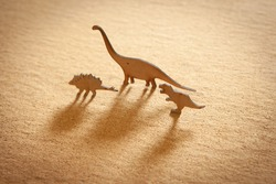 wooden dinosaurs silhouette on brown background.
