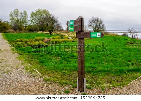 wooden direction indicator in the park with pictograms and distance signs #1559064785