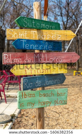 Wooden direction sign shows many directions
