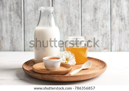 Wooden dish with milk and honey on table