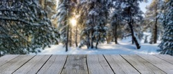 wooden display shelf table top against blurred sun rays shining through the snow covered pine trees in the winter forest, panoramic picture