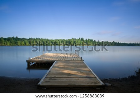Wooden dock on a calm lake at the cottage in Ontario, Canada. #1256863039