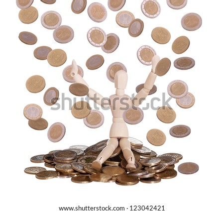 wooden doll sitting in rain of coins
