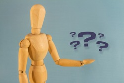 Wooden doll with his hand raised holding several question marks. Help desk or questions concept.