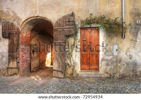 Wooden door and gate entrance to garage in old brick house in town of Saluzzo, northern Italy.