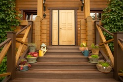 Wooden door and stairs of the house. Plants and watering can on a wooden staircase. Wild grapes on the wall of the house