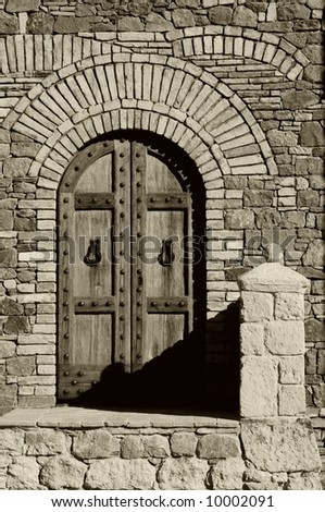 wooden door in a stone and brick building, sepia