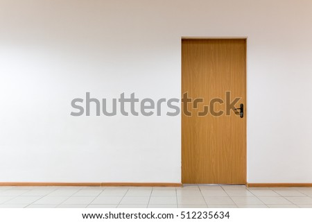 Wooden door on a clean wall indoors #512235634