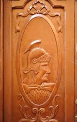 Wooden door with Roman soldier in profile in Cáceres, Extremadura, Spain
