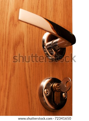Wooden doorway with shiny keyhole, key inserted