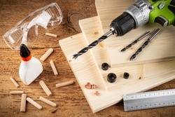 wooden dowel joint pins drill glue wood planks safety glasses cordless screwdriver and tools on rustic oak background. Carpenter industry funiture making concept.