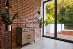 Wooden dresser in room with brick wall and big balcony door and window and garden view