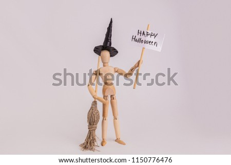 Wooden dummy jointed figure holding a Happy Halloween picket sign dressed up as a witch black witch hat and witch broom solid backdrop #1150776476