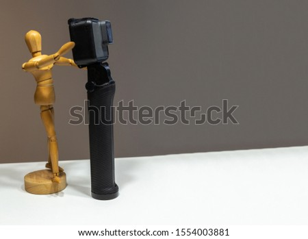 Wooden dummy photographing with a camera on a dark background