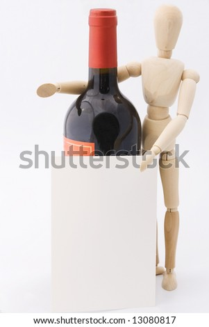 Wooden dummy presents red wine in bottle with blank message card