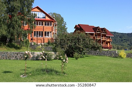Wooden dwelling-house and unfinished building. Altai. Russia.