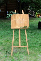 Wooden easel with a board. On the board written white paint - Welcome