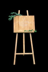 Wooden easel with a board. On the board written white paint - Welcome. Isolation on a black background
