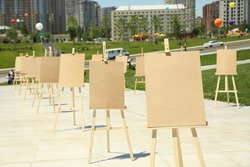 Wooden easel with blank canvas . Pair of Easel with blank canvas . Blank art board and realistic wooden easel outdoors. Drawing board easel blank exhibition at city street .