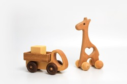 wooden eco-friendly toy giraffe on wheels and a truck with a cube in the back on a white background, place for text