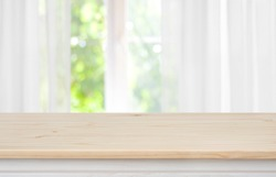 Wooden empty table in front of blurred curtained window background