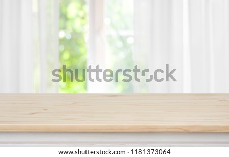 Wooden empty table in front of blurred curtained window background Foto d'archivio ©