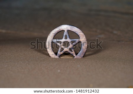 Wooden encircled Pentagram symbol on the beach at sunrise in front of the lake. Concept of Five elements: Earth, Water, Air, Fire, Spirit.