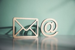 wooden envelope letter and e mail symbols on table