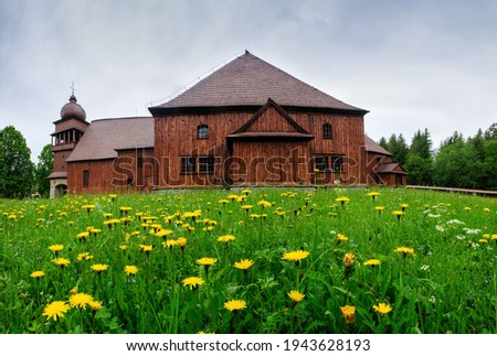Wooden evangelical articular church of the Svaty Kriz(Holy Cross), is one of the largest wooden churches in Europe.Green meadow, flowering dandelion, old architecture. Paludza, Svaty Kriz, Low Tatras Stok fotoğraf ©