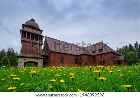 Wooden evangelical articular church of the Svaty Kriz(Holy Cross), is one of the largest wooden churches in Europe.Green meadow, flowering dandelion, old architecture. Paludza, Svaty Kriz,  Stok fotoğraf ©