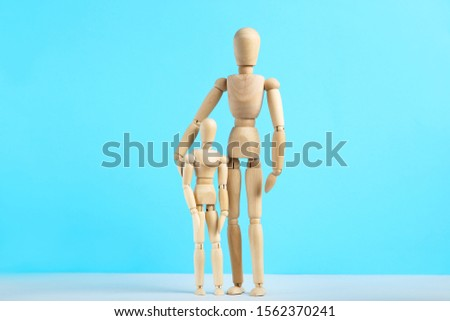 Wooden family figures on blue background #1562370241