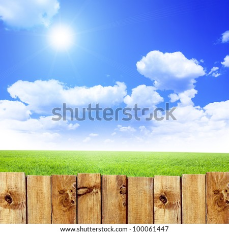 Wooden fence against green field and blue sky