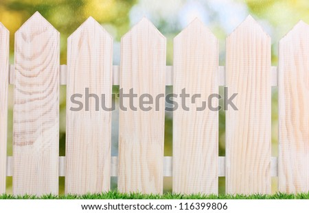 wooden fence and green grass on bright background